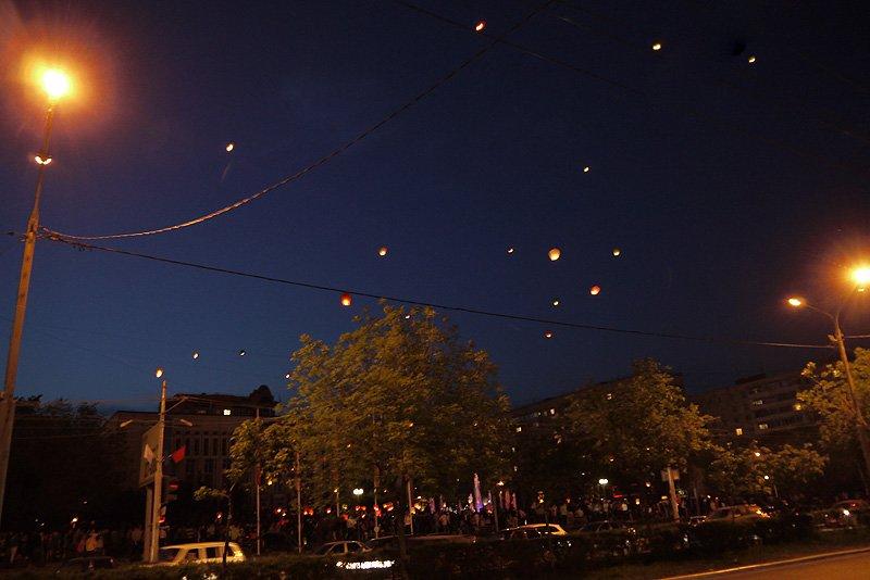 Радостная стайка весенних фонариков над толпой